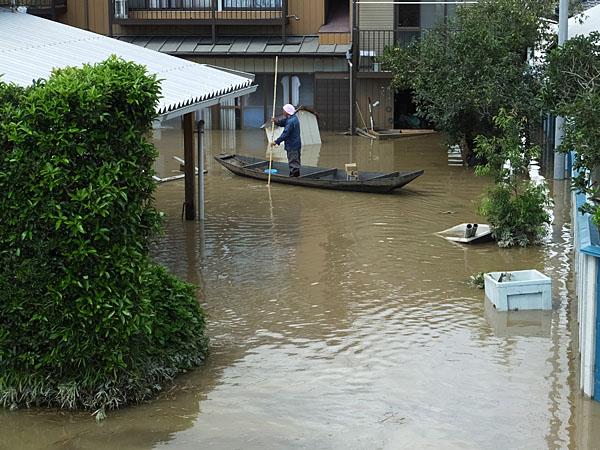 堤防から浸水した自宅まで小船で移動する人
